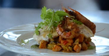 plated seafood dish with whole shrimp on top